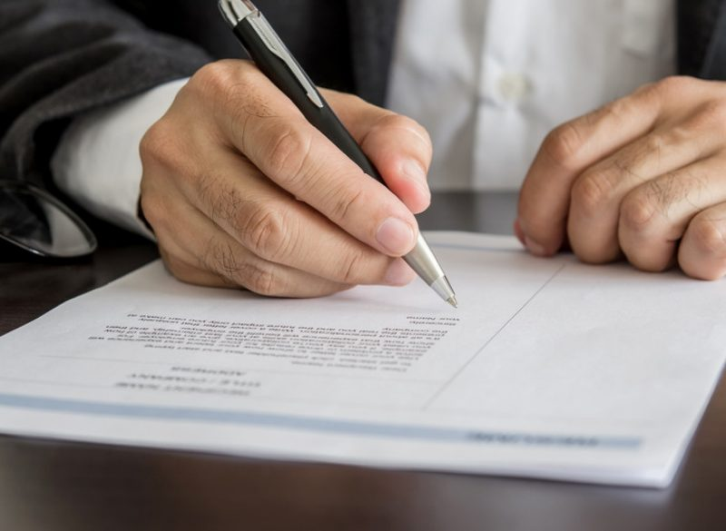 Close-up Businessman or job seeker signing on resume form.