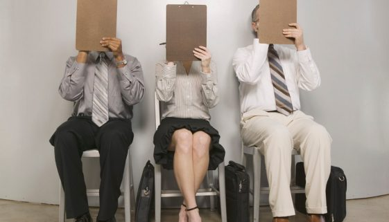 Job applicants with clipboards covering faces